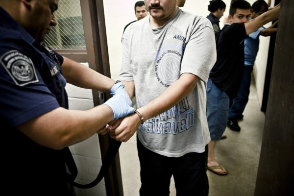 2. El sueño termina: migrantes indocumentados saliendo esposados de la celda.