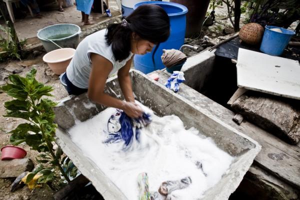 9. La hija de Leoncio lavando a mano la ropa sucia de toda la familia.